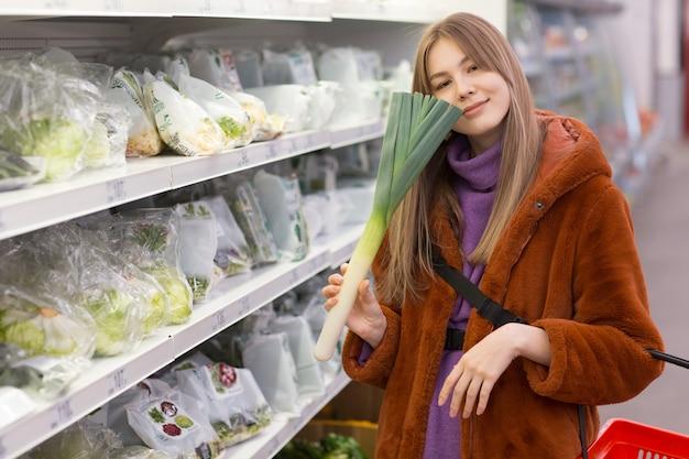Jonge vrouw met een boodschappenmand kiest producten op de groenteafdeling.
