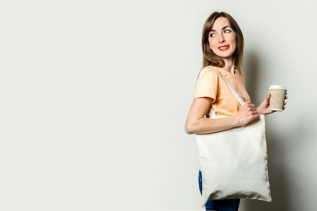 Jonge vrouw met een boodschappentas, houdt een papieren kopje met een kopje koffie, kijkt terug op een lichte achtergrond