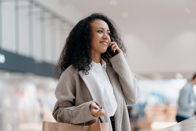 Jonge vrouw met een boodschappentas praat op een smartphone in een winkelcentrum