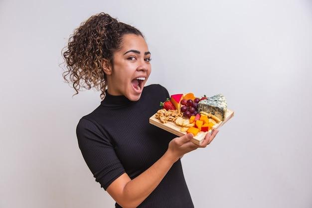 Jonge vrouw met een bord met verschillende soorten snacks kaas.