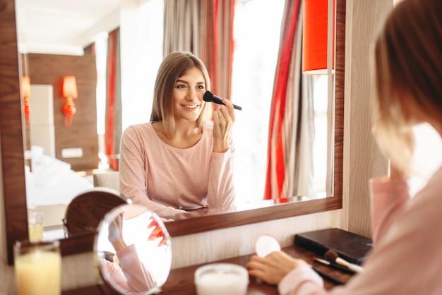 Jonge vrouw met een borstel in de hand die make-up voor de spiegel in de slaapkamer doet.