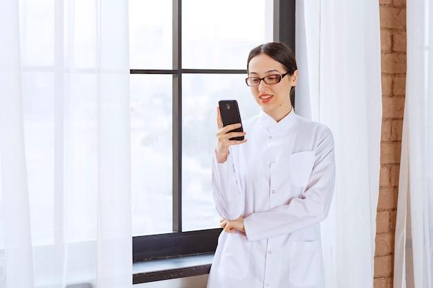 Jonge vrouw met een bril in laboratoriumjas die berichten op de mobiele telefoon in de buurt van het raam controleert.