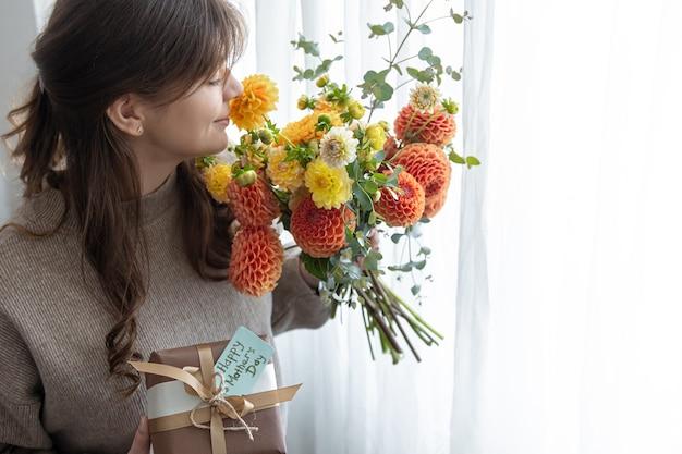 Jonge vrouw met een cadeau voor moederdag en een boeket bloemen in haar handen