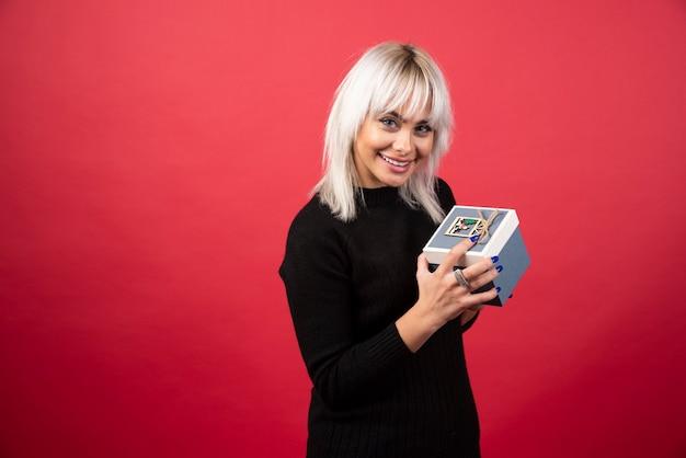 Jonge vrouw met een cadeautje op een rode muur.