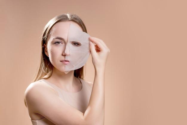 Jonge vrouw met een cosmetisch masker op haar gezicht op een bruine achtergrond.
