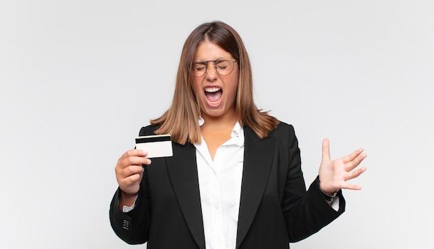 Jonge vrouw met een creditcard die agressief schreeuwt, erg boos, gefrustreerd, verontwaardigd of geïrriteerd kijkt, nee schreeuwt