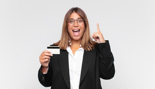 Jonge vrouw met een creditcard die zich als een gelukkig en opgewonden genie voelt na het realiseren van een idee, vrolijk de vinger opheffend, eureka!
