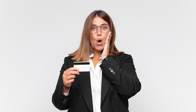 Jonge vrouw met een creditcard die zich geschokt en bang voelt en er doodsbang uitziet met open mond en handen op de wangen