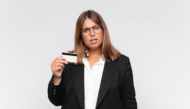 Jonge vrouw met een creditcard die zich verward en verward voelt, met een stomme, verbijsterde uitdrukking die naar iets onverwachts kijkt