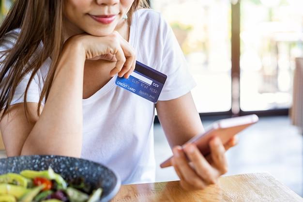Jonge vrouw met een creditcard en een smartphone