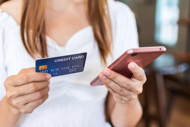 Jonge vrouw met een creditcard en het gebruik van smartphone voor het maken van online betalingen winkelen in restaurant