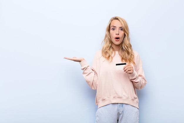 Jonge vrouw met een creditcard op zoek verrast en met een object met een open hand aan de zijkant