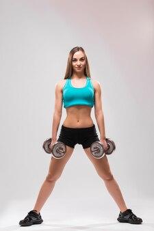 Jonge vrouw met een dummbell op grijze achtergrond