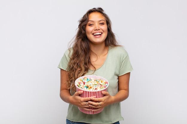 Jonge vrouw met een emmer met popconrs die er blij en aangenaam verrast uitzag, opgewonden met een gefascineerde en geschokte uitdrukking
