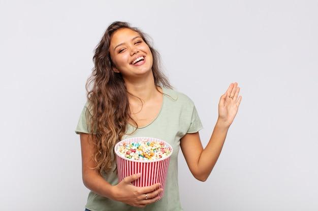 Jonge vrouw met een emmer met popconrs die vrolijk en opgewekt glimlacht, met de hand zwaait, je verwelkomt en begroet, of gedag zegt