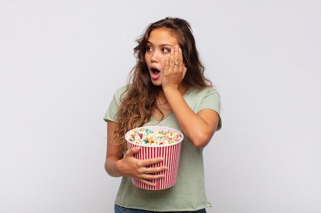 Jonge vrouw met een emmer met popconrs die zich blij, opgewonden en verrast voelt, naar de kant kijkend met beide handen op het gezicht