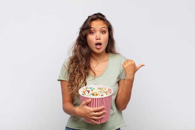 Jonge vrouw met een emmer met popconrs kijkt verbaasd van ongeloof, wijst naar een voorwerp aan de zijkant en zegt wow, ongelooflijk