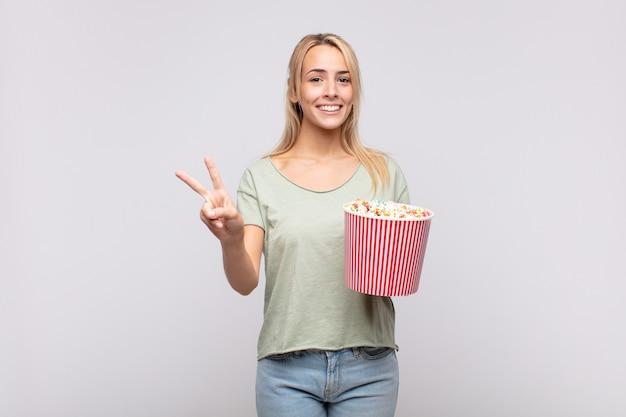 Jonge vrouw met een emmer met popcorn die lacht en er vriendelijk uitziet