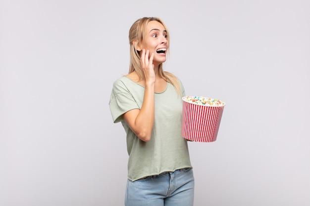 Jonge vrouw met een emmer met popcorn die zich blij, opgewonden en verrast voelt, opzij kijkend met beide handen op het gezicht