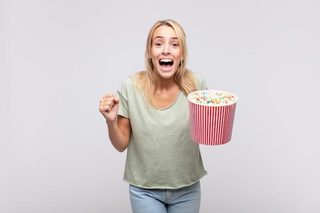 Jonge vrouw met een emmer met popcorn die zich geschokt, opgewonden en gelukkig voelt, lacht en succes viert, wauw zegt!