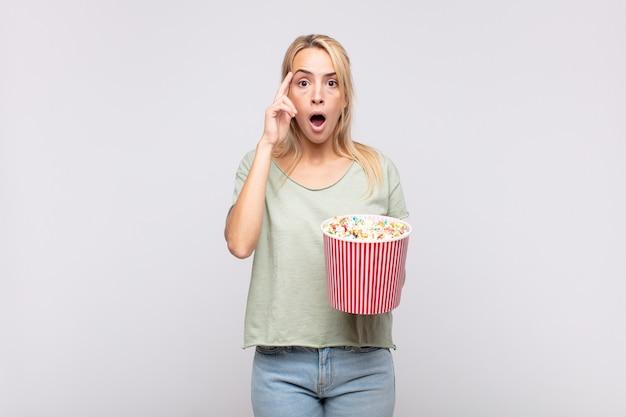 Jonge vrouw met een emmer met popcorn en kijkt verrast, met open mond, geschokt, realiseert zich een nieuwe gedachte, idee of concept