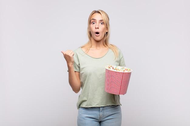 Jonge vrouw met een emmer met popcorn kijkt verbaasd van ongeloof, wijst naar een voorwerp op de zijkant en zegt wow, ongelooflijk