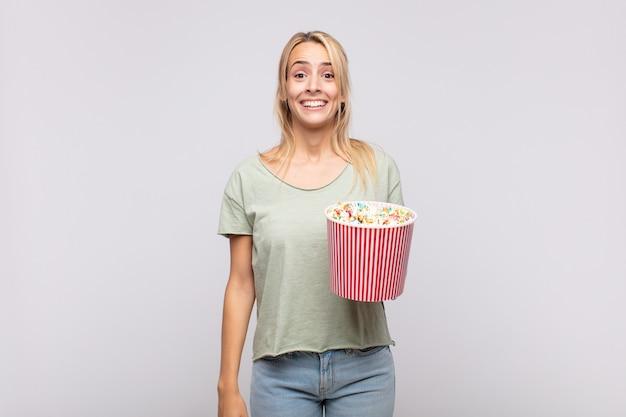Jonge vrouw met een emmer popcorn die er blij en aangenaam verrast uitzag, opgewonden met een gefascineerde en geschokte uitdrukking