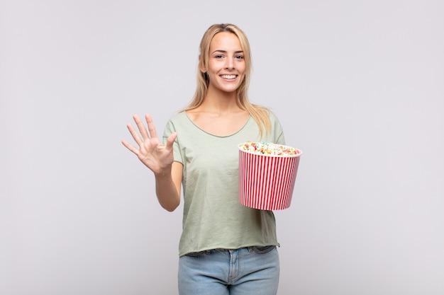 Jonge vrouw met een emmer popcorns die vriendelijk glimlacht kijkt, nummer vijf of vijfde met vooruit hand toont, aftellend