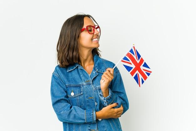 Jonge vrouw met een engelse vlag geïsoleerd op een witte muur glimlachend zelfverzekerd met gekruiste armen