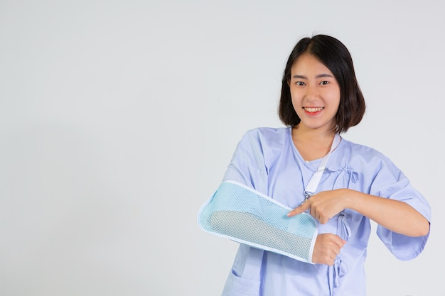 Jonge vrouw met een gebroken arm die een armspalk draagt