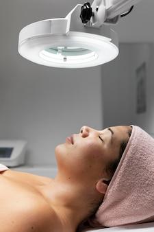Jonge vrouw met een gezichtsbehandeling in de schoonheidssalon