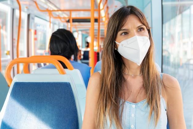 Jonge vrouw met een gezichtsmasker rijden openbaar vervoer.