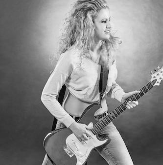 Jonge vrouw met een gitaar die een rocknummer uitvoert. zwart-wit foto