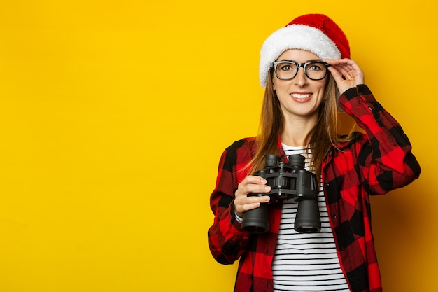 Jonge vrouw met een glimlach en in een kerstmuts en een rood shirt in een kooi houdt een verrekijker vast