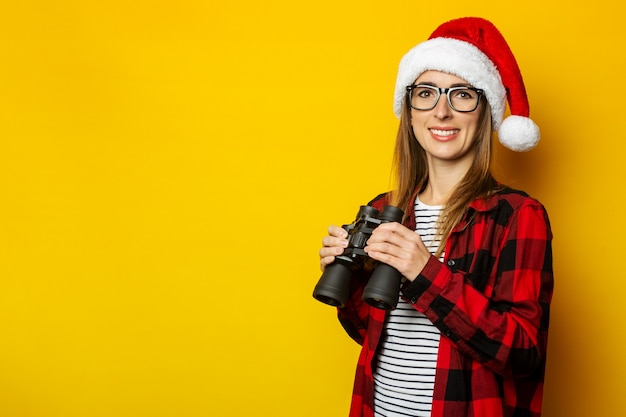 Jonge vrouw met een glimlach en in een santahoed en een rood overhemd in een verrekijker van de kooiholding