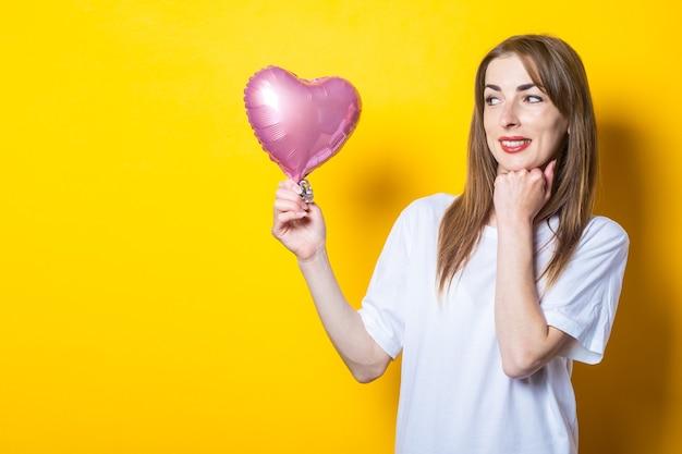 Jonge vrouw met een glimlach houdt een hartvormige ballon in haar handen en kijkt ernaar op een gele achtergrond. banner.