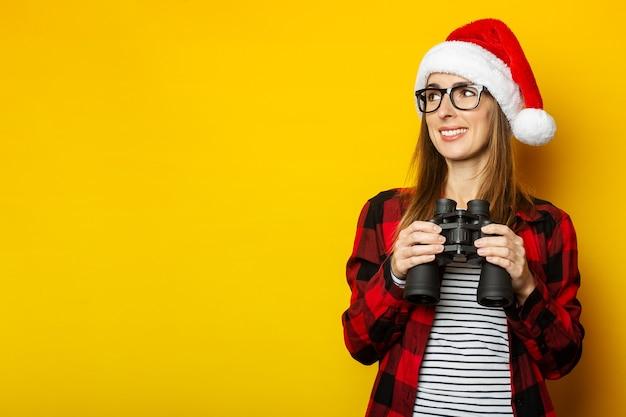 Jonge vrouw met een glimlach in een kerstmuts en een rood shirt in een kooi kijkt naar de zijkant en houdt een verrekijker vast