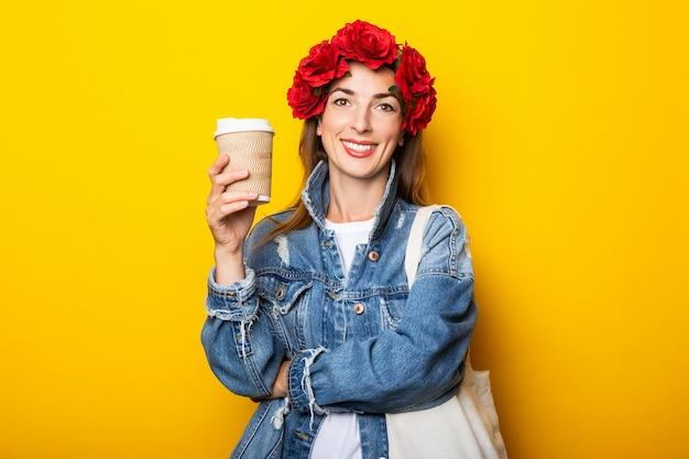 Jonge vrouw met een glimlach in een spijkerjasje en een krans van rode bloemen op haar hoofd houdt een papieren beker met koffie op een gele muur.