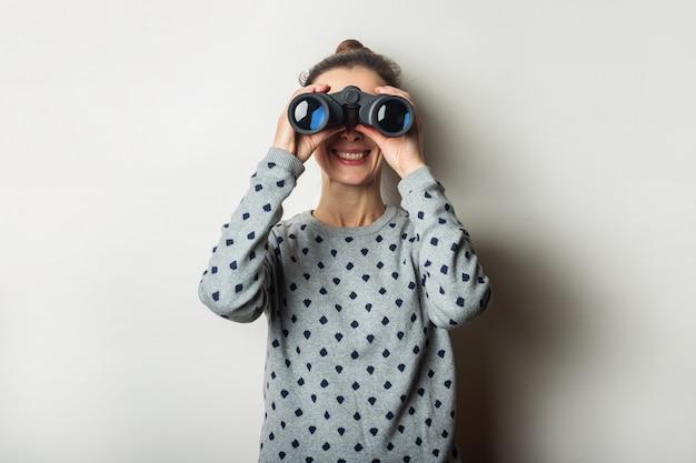 Jonge vrouw met een glimlach in een trui kijkt door een verrekijker op een lichte achtergrond.