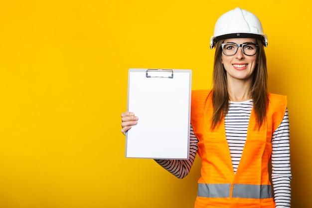 Jonge vrouw met een glimlach in een vest en bouwvakker houdt een klembord op geel