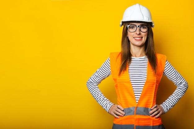Jonge vrouw met een glimlach in een vest en bouwvakker op geel