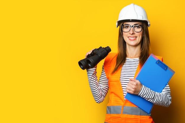 Jonge vrouw met een glimlach in een vest en een bouwvakker houdt een klembord en een verrekijker op geel