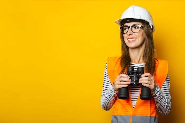Jonge vrouw met een glimlach in een vest en een helm houdt een verrekijker op geel