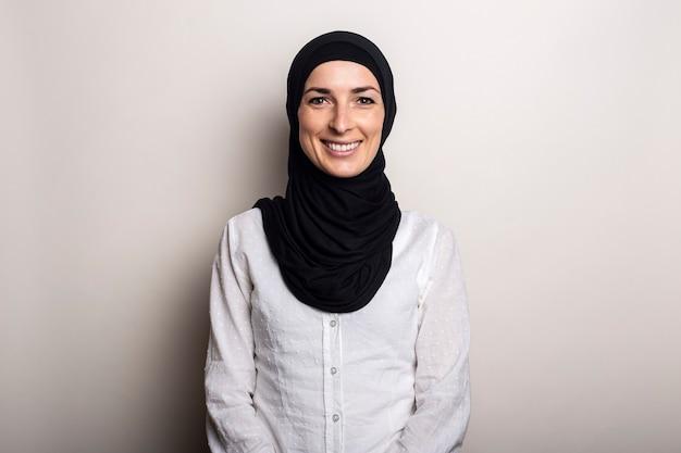 Jonge vrouw met een glimlach in een wit overhemd en hijab