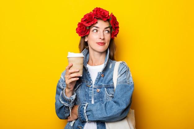 Jonge vrouw met een glimlach kijkt opzij in een spijkerjasje en een krans van rode bloemen op haar hoofd houdt een kartonnen beker met koffie op een gele muur.