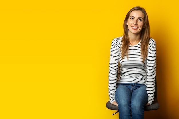 Jonge vrouw met een glimlach zit op een stoel o