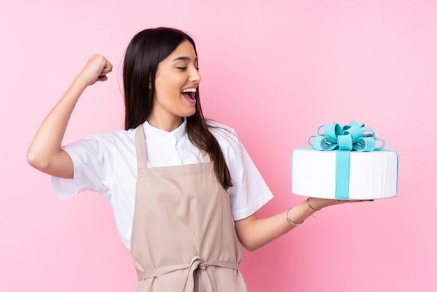 Jonge vrouw met een grote cake over geïsoleerde muur die een overwinning viert