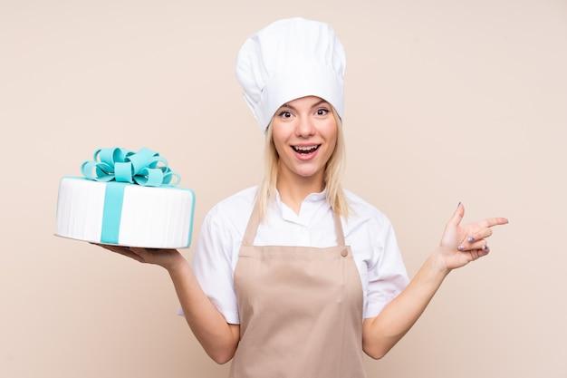 Jonge vrouw met een grote cake over geïsoleerde muur verrast en wijzende vinger aan de kant