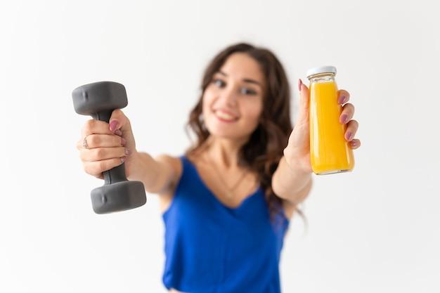 Jonge vrouw met een halter in haar hand en een fles