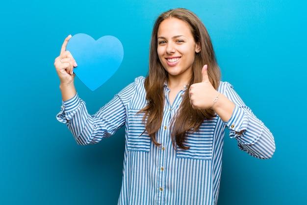 Jonge vrouw met een hartvorm tegen blauwe achtergrond